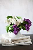 Fliederstrauß in weißer Vase auf Wäsche