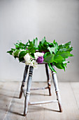 Wreath of lilac and lily-of-the-valley leaves on stool