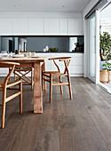 Designerstühle um rustikalen Holztisch in moderner Küche