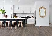 Bar stools at black island counter in white open-plan kitchen