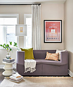 Purple sofa below framed advert and white side table below window