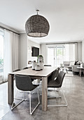 Upholstered chairs around dining table in interior in shades of grey and white