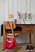 Old school chair at child's desk against board wall