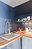 Rustic kitchen with grey walls under sloping ceiling