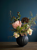 Wintry flower arrangement against dark blue wall