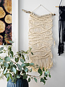 Knotted wall-hanging suspended from branch