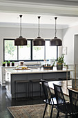Island counter, industrial-style pendant lamps and dining area in open-plan kitchen