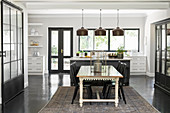 Dining area and industrial-style glass sliding door as partition in open-plan kitchen