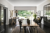 Dining area and lounge in front of open terrace doors in open-plan interior