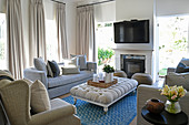 Pale upholstered furniture in front of fireplace and TV