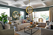 Pale upholstered furniture, coffee table, gilt pendant lamps and grey-green walls in living room