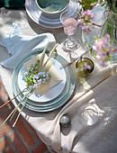 Blumen, Ähren und ein Umschlag auf dem Teller des gedeckten Tischs