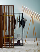 Coat rack and standard lamp behind screen