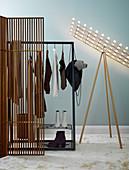 Coat rack and standard lamp behind screen