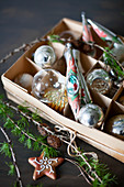 Christmas baubles in box, larch twig and star-shaped biscuit