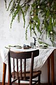 Lärchenzweige mit Weihnachtsdekoration über gedecktem Tisch