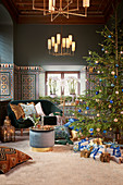 Christmas tree, gifts, side table and sofa in living room with colourful wall tiles