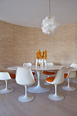 Round, white, classic Tulip table and matching chairs in dining area