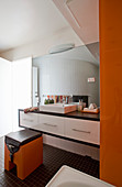 Washstand with countertop sink in bright bathroom with orange accents