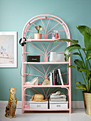 Pink rattan shelves against turquoise wall