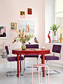 Chairs with purple upholstery around white table with fringed trim