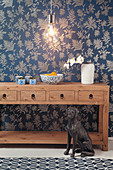 Wooden console table with drawers, light bulb lamp and dog sculpture against blue floral wallpaper