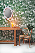 Wooden table and classic chair against leaf-patterned wallpaper