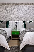 Green bedside table between twin beds with continuous headboard in bedroom