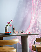 Concrete table, leather chairs and pink curtain