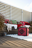 Cubic pouffe in front of bench with cushions on comfortable terrace