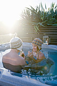 Man and woman wearing woolly hats in pool in sunshine