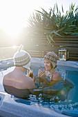Mann und Frau mit Mützen im Pool bei Sonnenschein