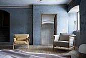 Sitzmöbel in grau-blauem Zimmer mit Holzdielenboden