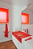 Rote Farbakzente im schlichten, weißen Bad