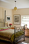Antique double bed in bedroom with cream walls
