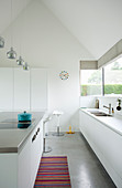 Minimalist, modern kitchen entirely in white below gable roof