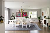 Designerstühle am weißen Tisch im eleganten Esszimmer mit Kamin