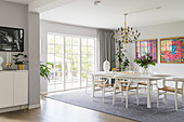 Designer chairs around white table in elegant dining room