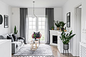 Klassisches Wohnzimmer in Grau und Weiß mit Eckkamin und Pflanzen