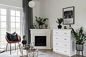 Zimmerpflanzen auf Kommode und Eckkamin im eleganten Wohnzimmer