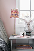 Table lamp with zigzag-patterned lampshade, feathers and mug with letter M