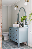 Washstand made from blue chest of drawers with mirror on top in country-house-style bathroom