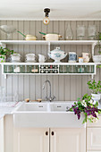 Kitchen sink and wall-mounted shelves in Scandinavian country-house kitchen