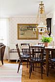 Nostalgisches Wohnzimmer mit Holzsofa und Petroleum-Deckenleuchte über Esstisch