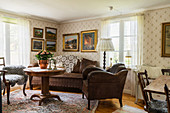 Collection of paintings above brown leather sofa in vintage-style living room