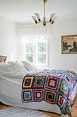 Multicoloured, crocheted granny-square blanket on double bed in vintage-style bedroom