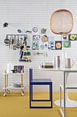 Checked wallpaper in kitchen with utensils on wall, serving trolley, table and chair