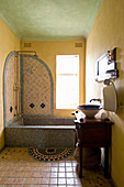 Mosaic-tiled bathtub in Oriental bathroom with yellow walls