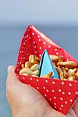 Selbstgebasteltes Papierboot zum Servieren von Knabbergebäck