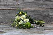 Bouquet of white pompom dahlias, grey santolina, houseleek rosettes and green tomatoes